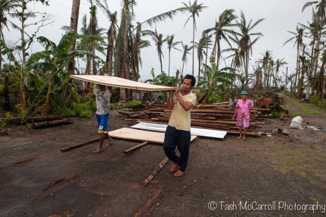 Village members collecting plywood to rebuild their homes from Ann's backyard.