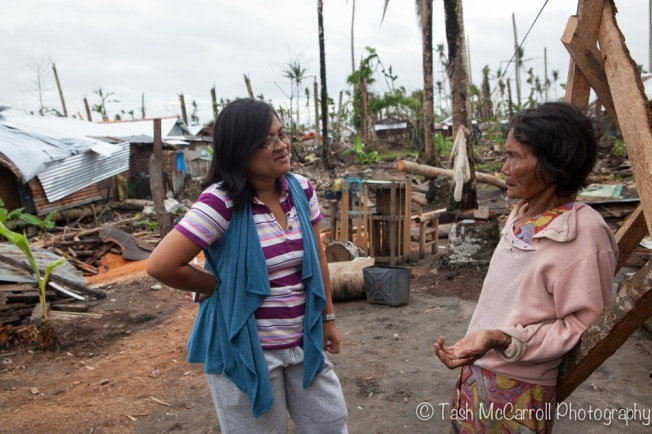 Ann speaks with a women from the village assessing her families needs.