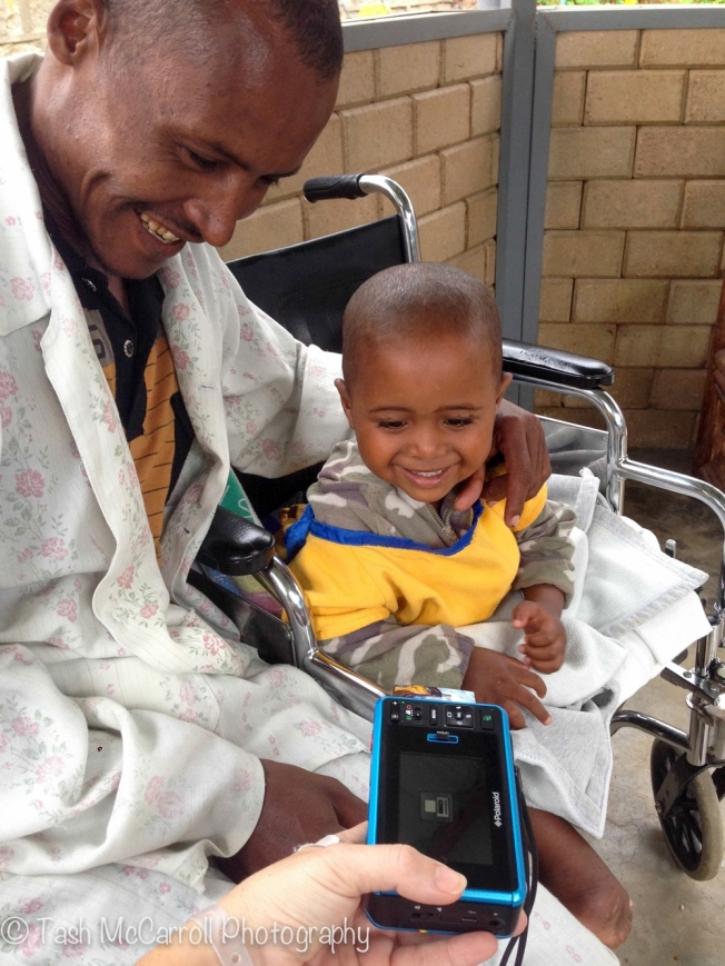 A young boy & his father at CURE Hospital in Addis Ababa Ethiopia watch their image print out