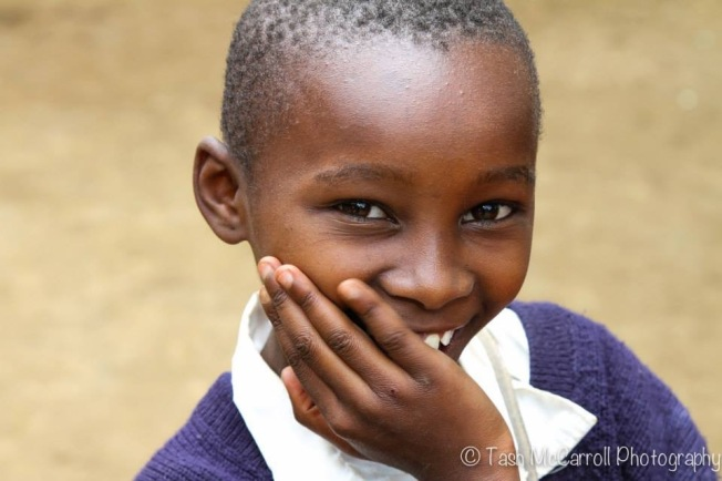 Shy schoolgirl hides her smile, Arusha, Tanzania (March 2014)