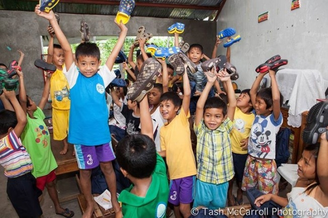 Small things make a huge difference. Children celebrate receiving new shoes after Typhoon Yolanda, Philippines (February 2014)